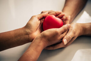 Two interlinked hands holding a heart